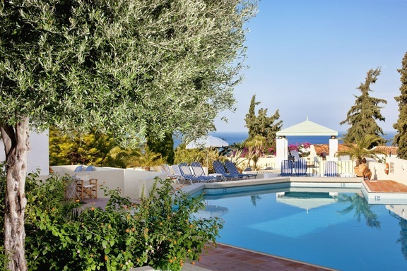 Pool and garden with sun loungers and parasols at Galaxy Villas in Koutouloufari, a lovely villa complex and family friendly hotel in Hersonissos