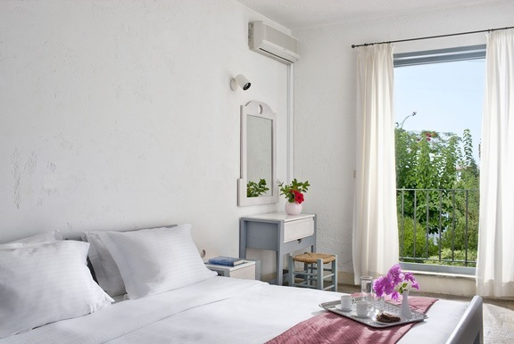 Bedroom view onto the balcony overlooking the verdant garden at one of the villas in Hersonissos Crete of Galaxy Villas